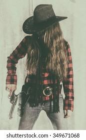 Cowgirl Gunslinger Holding Gun. Old west cowgirl gunslinger standing, holding peacemaker gun at her side, edited in vintage film style.