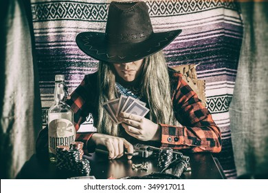 Cowgirl Gunslinger Poker Cards. Old west cowgirl gunslinger sitting at table player poker with peacemaker gun, edited in vintage film style.