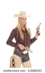 A cowgirl in her chaps holding on to her two pistols with a serious expression.