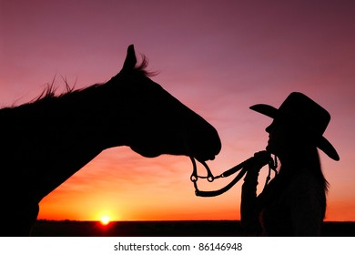 A cowgirl and her horse as the sun sets in the distance against a very colorful and dramatic sky.