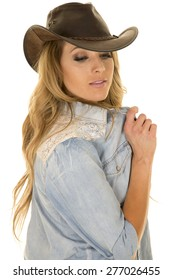 a cowgirl with her western hat on , playing with her shirt.