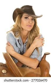 a cowgirl with her western hat on, leaning on her saddle.