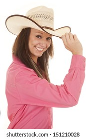 A cowgirl holding on to the rim of her hat with a smile on her face.