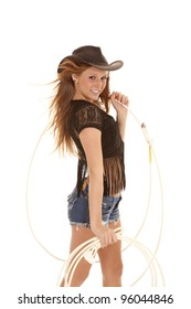 A cowgirl holding a rope  with a huge smile on her face.