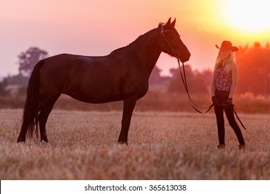 Cowgirl with a horse at sunset.