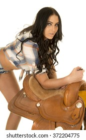A cowgirl leaning over her saddle looking serious.