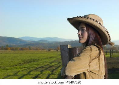 Cowgirl looking over fence with a Fall background with copy space