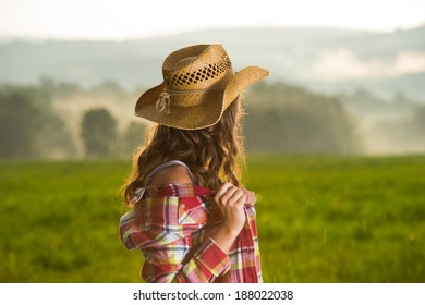Cowgirl looking over foggy field in rain