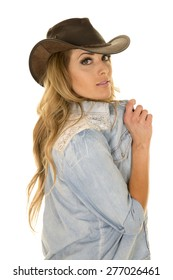 A cowgirl looking over her shoulder holding out her collar on her shirt.