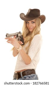 A cowgirl with a mischievous expression on her face pointing her pistol.