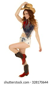 A cowgirl playing and dancing with a leg up wearing her western hat.