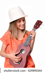 Cowgirl playing ukulele on a wooden chair, isolated on white background. Little girl with ukulele guitar.