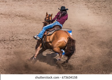 Cowgirl riding her horse in a barrel racing contest.