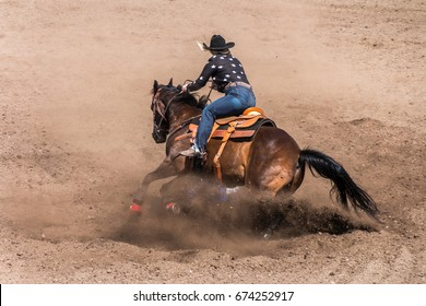 Cowgirl riding her horse in a barrel race at a rodeo