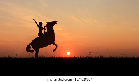 Cowgirl riding a horse, rearing up at sunset. Stallion standing on hind legs at horizon line with setting sun. Image for site header, banner