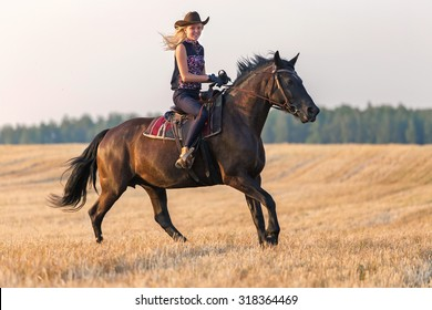 Cowgirl riding a horse at sunset.