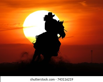 cowgirl riding at sunset