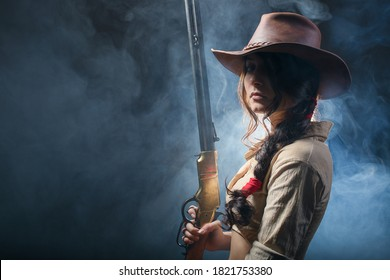 Cowgirl with rifle from wild west in the dark background