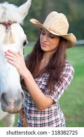 Cowgirl rubbing her horse