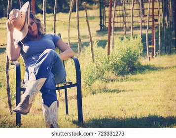 Cowgirl sitting in chair outside wearing western wear clothing and cowboy hat.