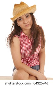 A cowgirl sitting on a bench with a serious expression on her face.