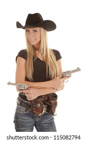 A cowgirl standing with her pistols in her hands and her holsters on her hips.