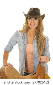 A cowgirl standing next to her saddle with a big smile on her lips.