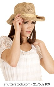 A cowgirl touching the brim of her hat looking.