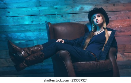 Cowgirl Wearing blue jeans and brown hat. Sitting on leather chair. In front of wooden wall.