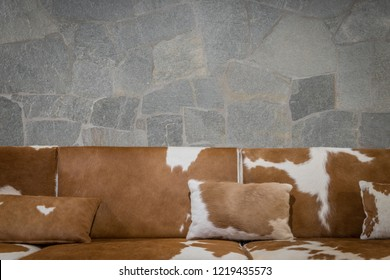 Cowhide sofa against stone wall