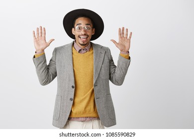 Coworker being caught on stealing food. Portrait of funny good-looking african guy in trendy black hat and stylish jacket, raising palms in surrender, being uninvolved and clueless over gray wall