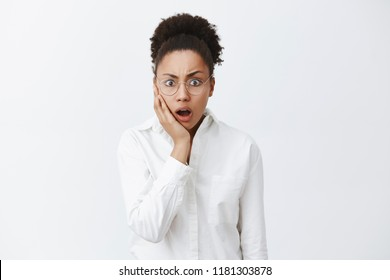 Coworker came work in blood, woman being stunned and shook. Portrait of shocked intense african-american female employer in white-collar shirt dropping jaw and gasping, staring amazed over grey wall