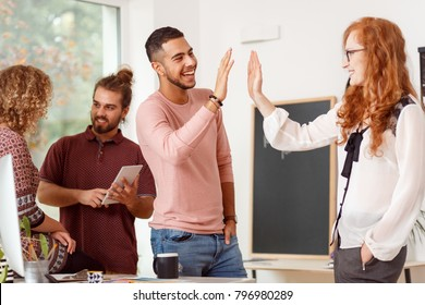 Co-worker giving his colleague a high five after work in multicultural group in corporation's office