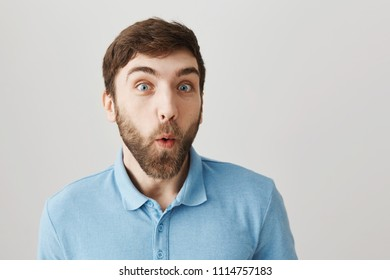 Coworker hearing dirty rumors about his boss. Amazed and intrigued young caucasian man making wondered and interested face while listening gossips in office, standing over grey background