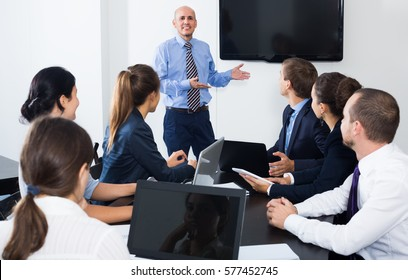 Coworker making presentation during business meeting in office