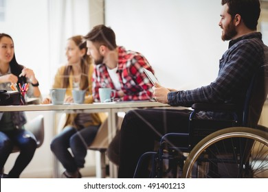 Coworker on wheelchair using digital tablet against photo editors in meeting room at creative office