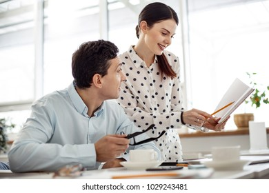Co-workers. Beautiful happy dark-haired young woman smiling and showing her notebook to a man sitting at the table and holding glasses