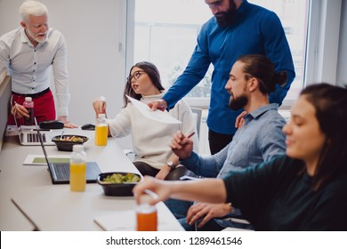 Coworkers discussing about work and having lunch in the office