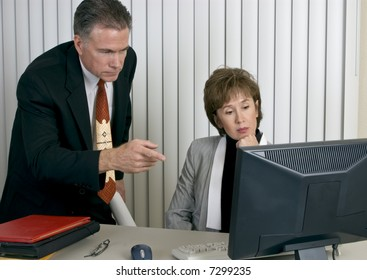 Co-workers discussing or analyzing something on a computer monitor.