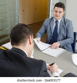 Co-workers discussing business plan in office