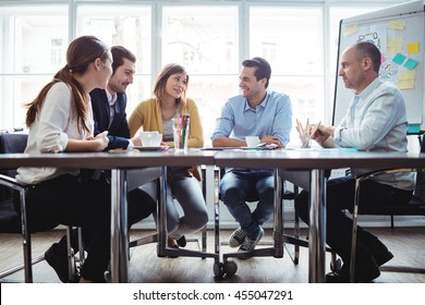 Coworkers discussing in meeting room at creative office