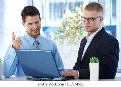 Coworkers discussing work in office, businessmen using laptop computer, concentrating on screen.