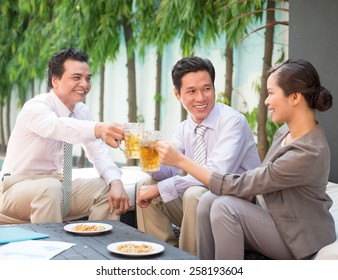 Coworkers drinking beer and chatting outdoors
