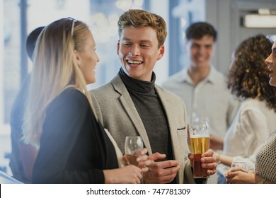 Coworkers are enjoying drinks in a bar after work. A man is holding a pint of beer and is talking to a woman who has her back to the camera.