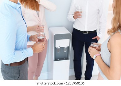 Co-workers having break near water cooler on white background, closeup