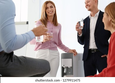 Co-workers having break near water cooler at workplace