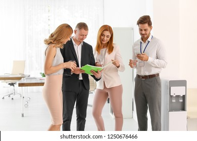 Co-workers having meeting near water cooler at workplace