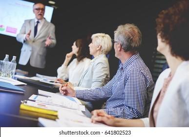 Coworkers listening to male public speaker