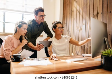 Coworkers looking at a computer and discussing over new business plan. Business team working together on computer in office.