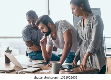 Coworkers looking at a laptop and discussing over new business plan. Business team working together on computer in office.